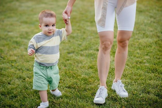 Молодая милая мама помогает и учит своего маленького сына делать первые шаги во время заката в парке на траве.