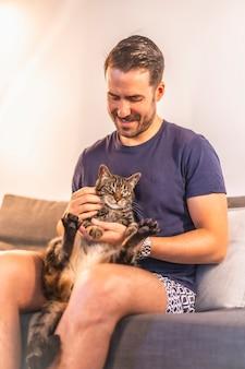 파란색 티셔츠와 반바지 그의 아름다운 회색 및 흰색 국내 고양이 함께 집에서 놀고있는 어린 검은 머리 백인 남자. 고양이 남자의 가장 친한 친구. 예쁜 고양이 쓰다듬어
