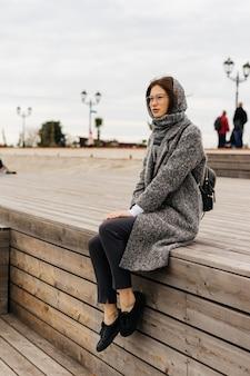 Молодая темноволосая девушка в сером пальто и очках сидит на деревянной террасе у моря, наслаждаясь пасмурной погодой.