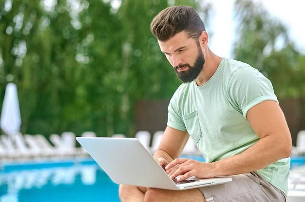 수영장 근처에 앉아 노트북 작업을 하는 검은 머리 청년