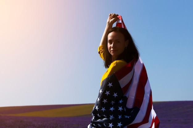 Молодая темноволосая женщина держит флаг соединенных штатов америки на фоне солнечного неба. день памяти и концепция день независимости сша.