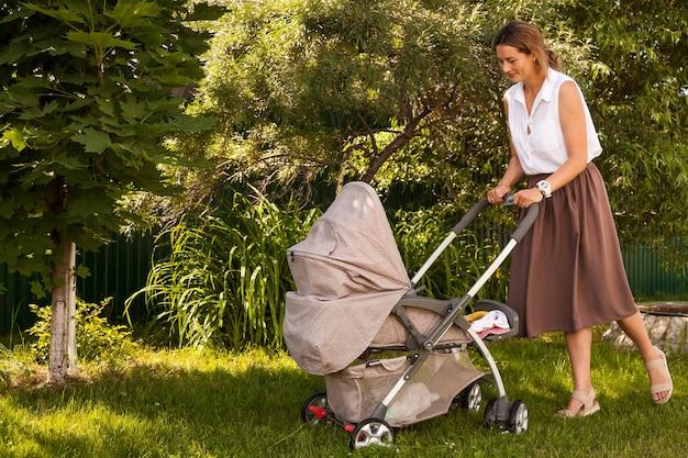 ベージュのスカートの白いシャツを着た若い黒髪の女性は、公園で夏の明るい日にベビーカーで小さな赤ちゃんと一緒に歩いています