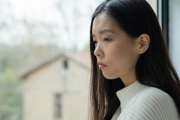 Молодая разочарованная азиатская женщина сидит в доме и смотрит в окно