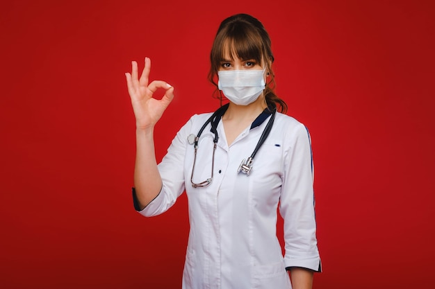 白衣と医療マスクの若い医者は赤い背景の上に立っています