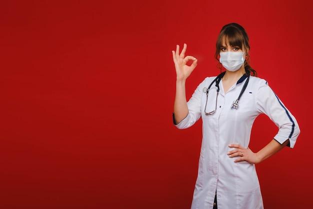 Молодой врач в белом халате стоит на красном фоне и показывает рукой знак ок, и все будет хорошо. врач показывает, что все в порядке.