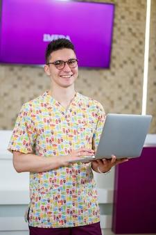 Молодой врач работает на ноутбуке над диссертацией. врач в клинике ведет онлайн-прием пациентов