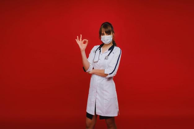 Молодой врач стоит на красном фоне и показывает руку, все будет хорошо. врач показывает ок.