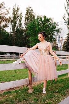 Юная нарядная балерина ставит ногу на деревянный забор и завязывает ленточки на пуантах в па ...