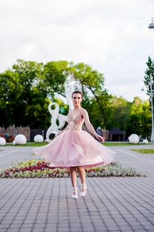 Юная нарядная балерина танцует в парке, пышная юбка из органзы разлетается на ...