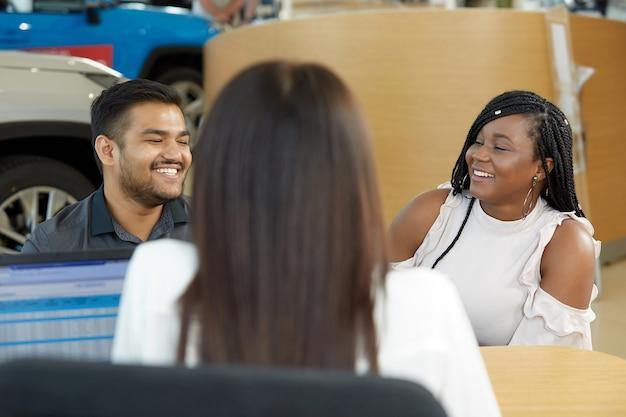 若い感情的なアフリカ系アメリカ人のカップルは、自動車のショールームで女の子のセールスマネージャーと通信します
