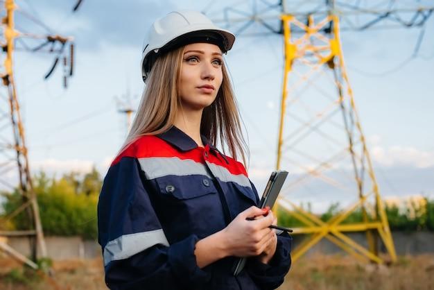 若いエンジニアリングワーカーが電力線の機器を検査および制御します。エネルギー。