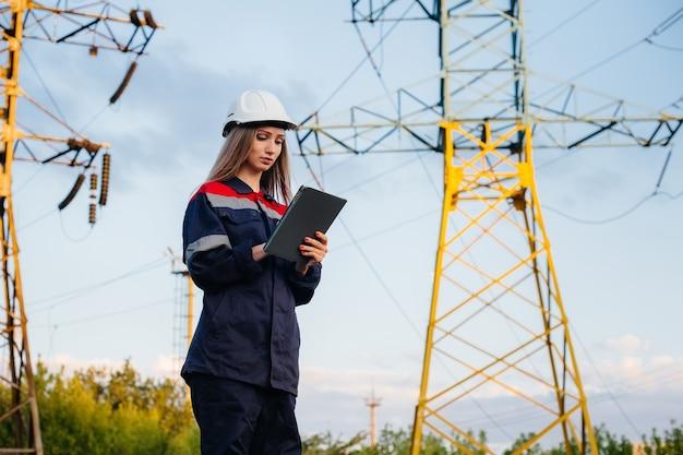 Молодой инженер-технолог осматривает и контролирует оборудование лэп. энергия.