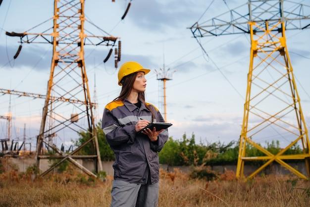 若いエンジニアリングワーカーが電力線の機器を検査および制御します