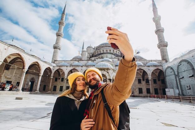 Молодая европейская пара гуляет во дворе голубой мечети и делает селфи, стамбул, турция. парень и девушка путешественника в желтых шляпах фотографируются в зимнем стамбуле.