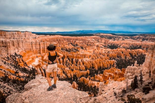 ブライス国立公園のブライスポイントから国立公園を見ている若いヨーロッパの女性。ユタ、米国