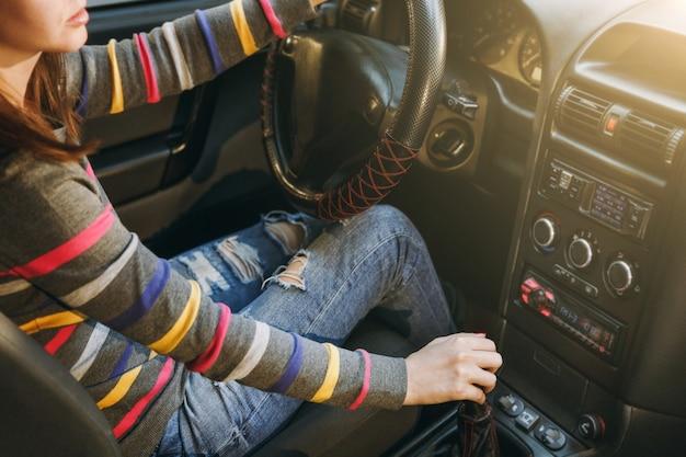 Молодая европейка со здоровой чистой кожей, одетая в полосатую футболку, сидит в своей машине. крупным планом выстрел. концепция путешествия и вождения.