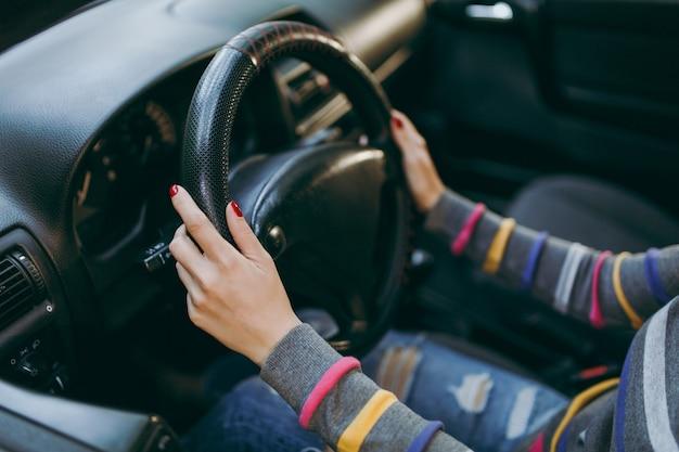 건강하고 깨끗한 피부를 가진 젊은 유럽 여성은 검은색 인테리어가 있는 자동차의 운전대에 손톱에 빨간 매니큐어로 손을 대었습니다. 여행 및 운전 개념입니다.