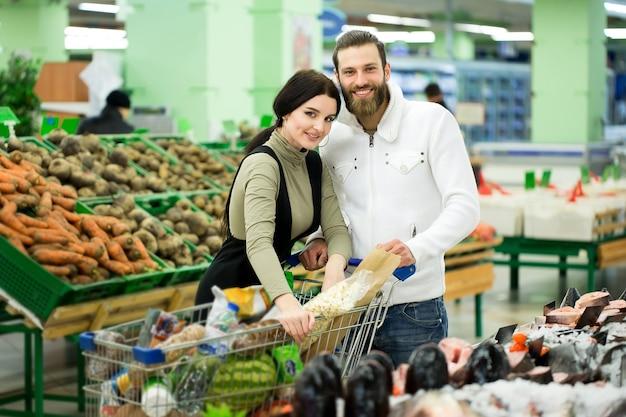 Молодая семья, мужчина и женщина выбирают рыбу в большом супермаркете.