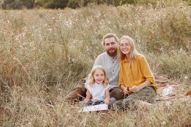 自然の中でピクニックをしている若い家族。児童保護