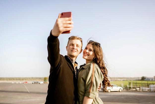 Молодая семейная пара, делающая селфи во время каникул по европе, улыбаются красивые люди