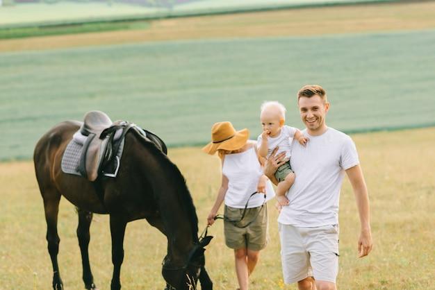 젊은 가족은 현장에서 즐거운 시간을 보냅니다. 말과 함께 부모와 자식