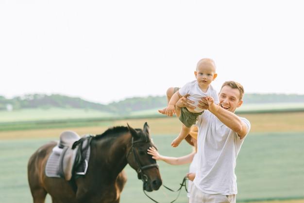 若い家族がフィールドで楽しんでいます。馬を持つ親子
