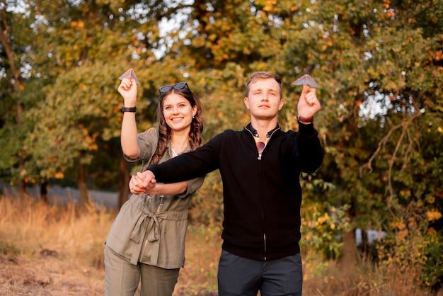 屋外で楽しんでいる若い家族、紙飛行機を投げて、幸せを感じて、笑顔で笑ってください