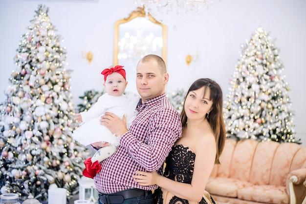 雪に覆われたクリスマスツリーを背景に小さな赤ちゃんを腕に抱いている若い家族