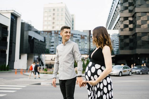 Молодая семья ждет малыша. муж и жена смотрят друг на друга, пока идут по центру города.