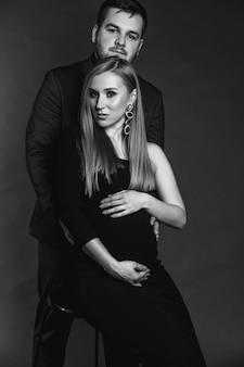 若い家族が子供の誕生を待っています。男と妊娠中の女性は互いに立ち向かい、茶色の無地の背景に抱いています。幸せなカップルを愛する。妊娠