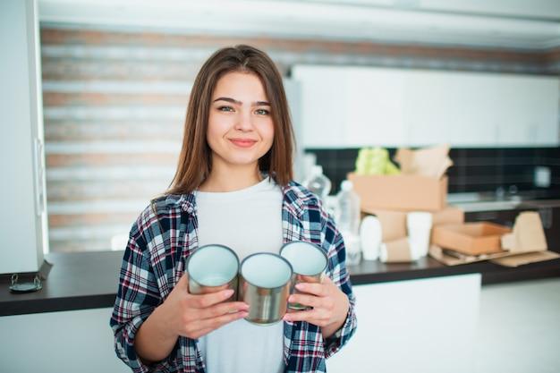 若い家族がリサイクルのために台所で材料を分類します。リサイクル可能な材料は分別する必要があります。食べ物のために彼女の手で古い缶を保持している若い女性。