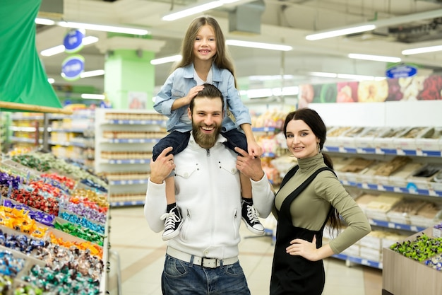 Молодая семья с маленькой девочкой выбирают конфеты и шоколад в большом магазине-супермаркете.