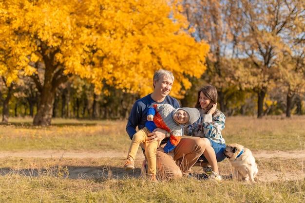 Молодая семья с маленьким ребенком и собакой вместе гуляют в осеннем парке