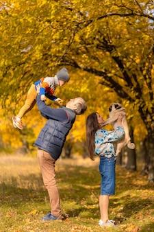 Молодая семья с маленьким ребенком и собакой вместе гуляет в осеннем парке.