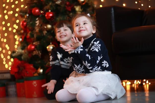 Молодая семья с детьми украшает дом к празднику нового года.