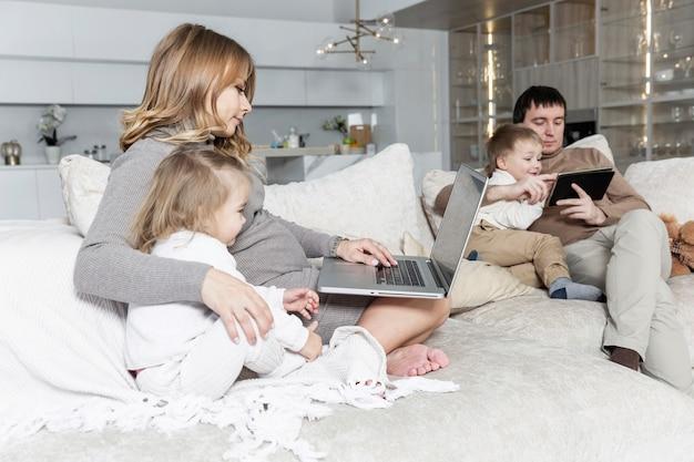 어린 자녀를 둔 젊은 가족이 가제트가있는 거실에서 휴식을 취하고 있습니다.