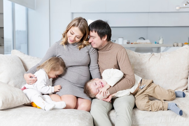 작은 아이들이있는 젊은 가족이 거실의 소파에 앉아 웃고 포옹합니다.