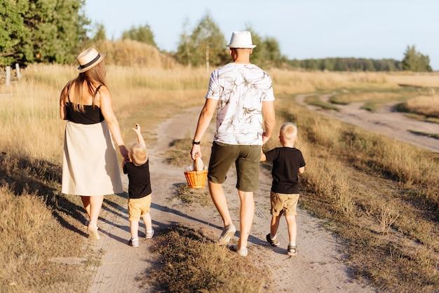 2人の子供を持つ若い家族は夏に街の外で自然の中を歩きます