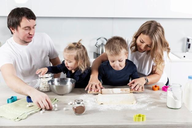 부엌에 두 명의 작은 아이들이있는 젊은 가족이 쿠키 반죽을 준비하고 웃고 있습니다.