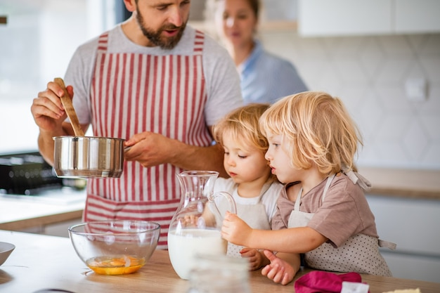キッチンの屋内で料理をしている2人の小さな子供を持つ若い家族。