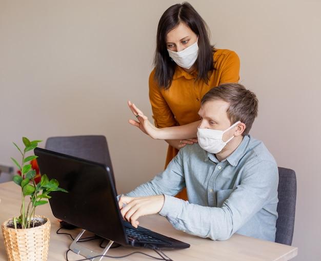 Молодая семья работает из дома за компьютером. изолированная пара коронавирусов в медицинских масках. призыв остаться дома в безопасности. заказать продукты питания онлайн. ноутбук фрилансер спор бизнес офис