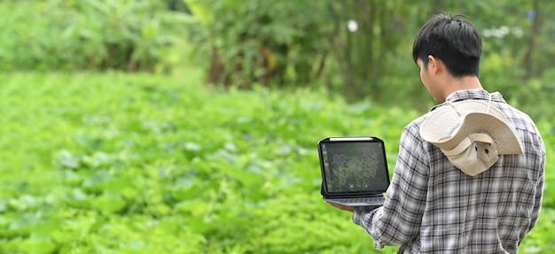 Молодой фермер использует портативный компьютер, стоя среди фруктового сада.