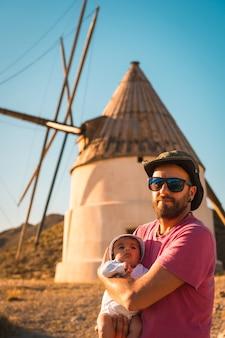 Молодой отец наслаждается с сыном в природном парке кабо-де-гата на мельнице в городе сан-хосе, альмерия.