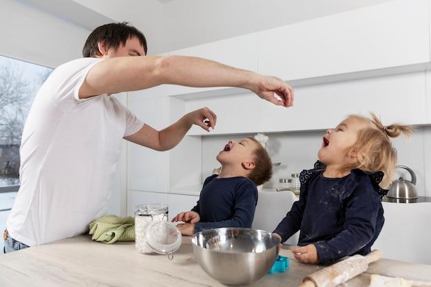 젊은 아버지는 부엌에서 열린 입으로 어린 아이들에게 먹이를줍니다.