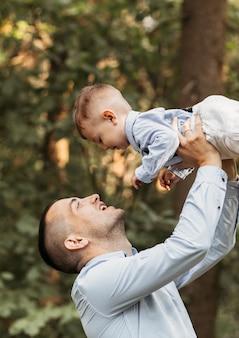 Молодой отец летом держит на руках маленького сына на природе. объятия и поцелуи