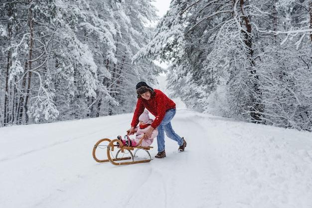 赤いセーターを着た若い父親が、雪に覆われた森で魅力的な娘と一緒に木製のそりに乗ります。
