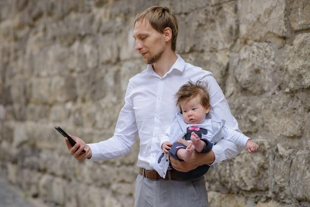 若い父親が携帯電話で話しており、小さな娘を両腕に抱えています。コピースペース