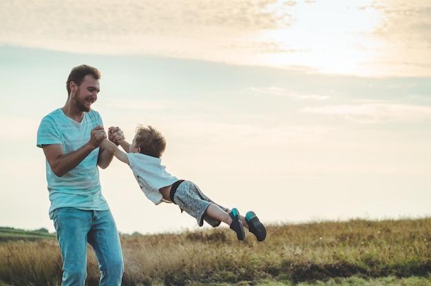 Молодой отец бросает маленького сына на вечернее солнце. день отца. отец держит маленького сына, крутит его. лето осенняя природа.