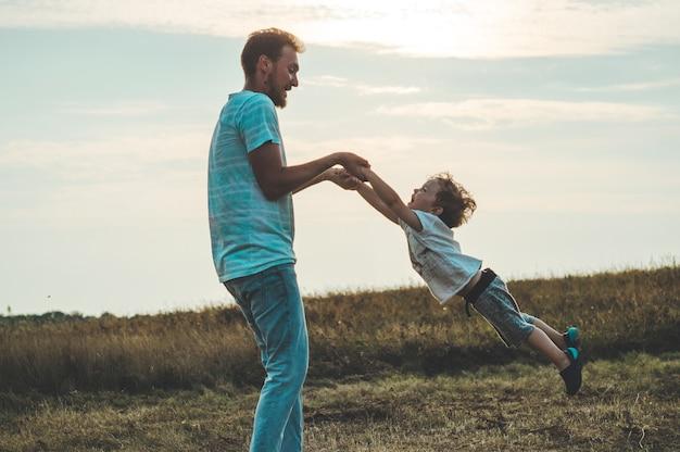 한 젊은 아버지가 어린 아들을 저녁 햇살에 던졌습니다. 아버지의 날. 그의 작은 아들을 안고 그를 회전시키는 아버지. 여름 가을 자연.
