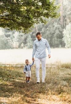 Молодой отец с маленьким сыном на природе летом. объятия и поцелуи